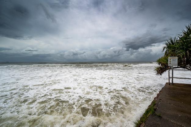 Ferida espumosa sob céu escuro e nublado em alexandra headland beach, queensland, austrália