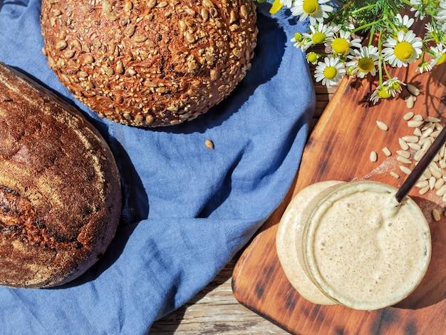 Fermento para pão em uma jarra de vidro e pães caseiros