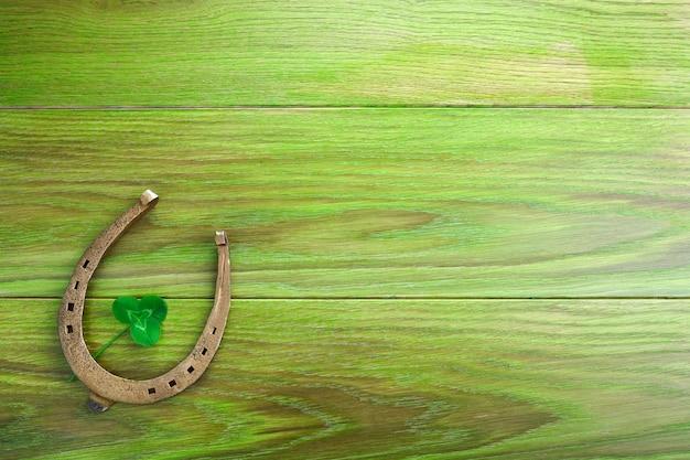 Ferradura e trevo sobre fundo verde de madeira. trevo de quatro folhas verdes. símbolo do dia de são patrício.