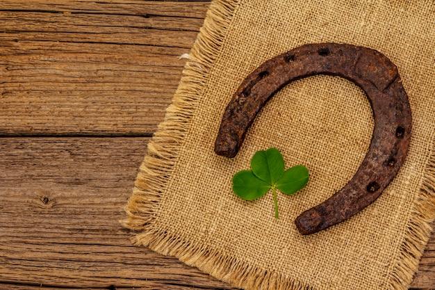 Ferradura muito velha do cavalo do metal do ferro fundido, folha fresca do trevo. símbolo de boa sorte, conceito do dia de st.patrick
