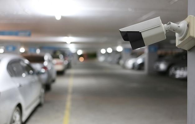 Ferramenta cctv no fundo do estacionamento automóvel, equipamento para sistemas de segurança e espaço de cópia para o design.
