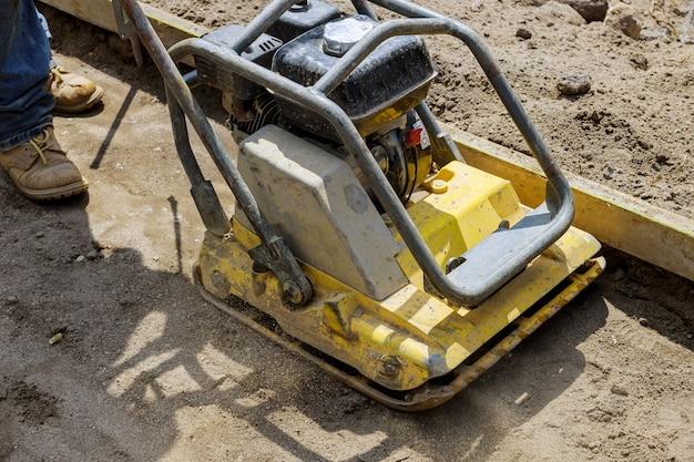 Ferramenta compactadora de placa vibratória na areia em construção compactando na calçada