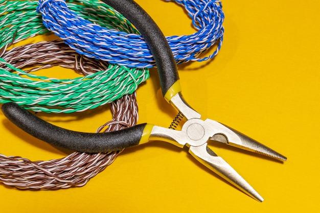 Ferramenta de alicate e fios para conceito de reparo de serviço de eletricista closeup em fundo amarelo closeup
