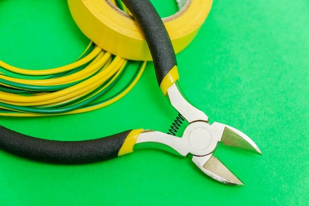 Ferramenta de alicate e fios para eletricista close-up em espaço verde