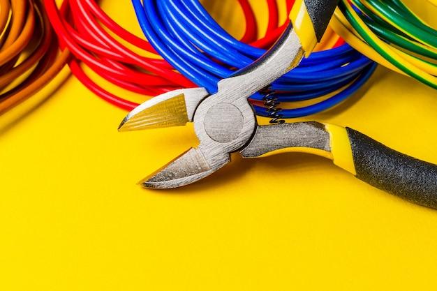 Ferramenta de alicate e fios para eletricista closeup, conceito de serviço e reparo no espaço amarelo