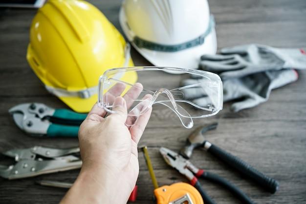 Ferramenta de artesão, para homem trabalhador. óculos de segurança na mão