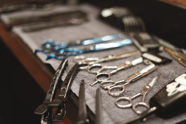 Ferramenta de barbeiro na barbearia. ferramenta de cabeleireiro. tesouras, pentes, lâminas de barbear, tosquiadeiras. ferramenta para o assistente. organização do local de trabalho.