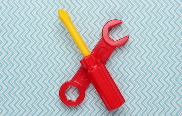 Ferramenta de brinquedo infantil. chave inglesa, chave de fenda em um pastel azul