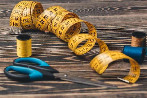 Ferramenta de costura com linhas coloridas, medidor e tesoura