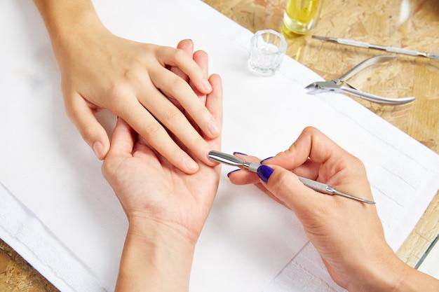 Ferramenta de empurrador de cutícula nas mãos de mulher de salão de beleza de unhas