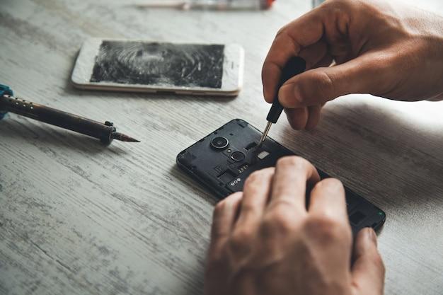 Ferramenta de mão de homem com telefone quebrado na mesa