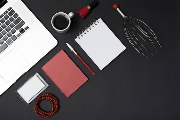 Ferramenta de massagem; computador portátil; papelaria; xícara de café; pulseira e verniz de unhas sobre a mesa preta