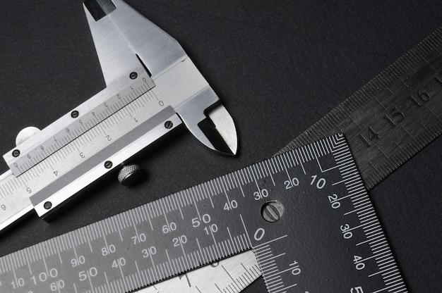Ferramenta de medição, régua quadrada e compasso de calibre. mentir sobre um fundo escuro. fechar-se.