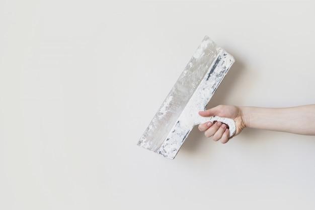 Ferramenta de trabalho, espátula na mão sobre um fundo claro, estucador de trabalho, pintor, para fazer reparos. pá de pedreiro na mão do homem em um fundo de uma parede branca. espaço para texto