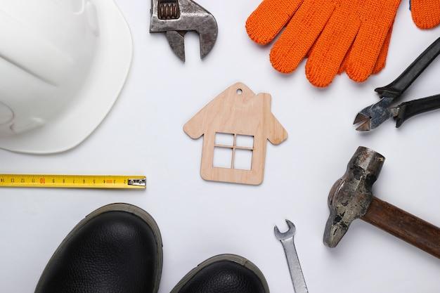 Ferramenta doméstica diy. ferramentas de construção e figura de casa em fundo branco. composição plana lay. vista do topo