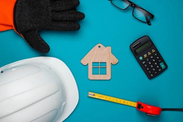 Ferramenta doméstica diy. ferramentas de construção, equipamentos de engenharia e figura da casa sobre fundo azul. composição plana lay. vista do topo