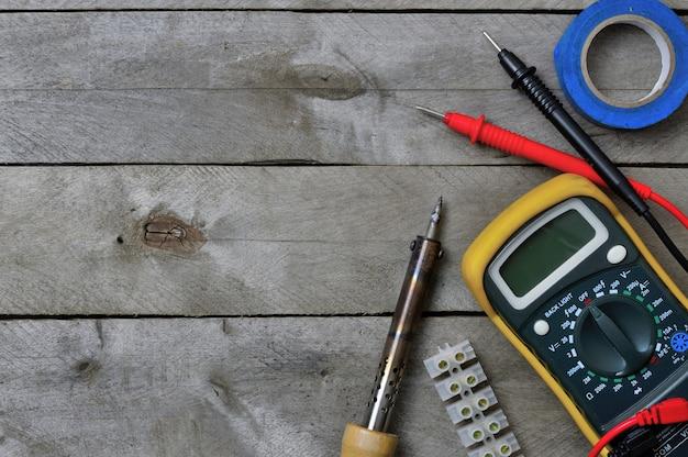 Ferramenta elétrica e testador em um fundo de madeira. copie o espaço