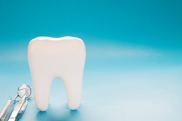 Ferramenta grande do dente e do dentista no fundo azul.