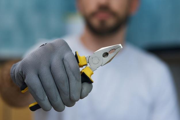 Ferramenta manual necessária, close-up tiro da mão de um jovem reparador segurando um alicate