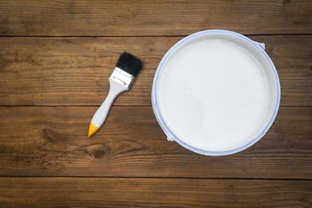 Ferramenta pintada com pincel balde de tinta enlatada para pintura em fundo de madeira, vista superior