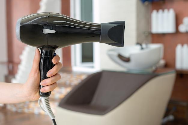 Ferramenta profissional do cabeleireiro do secador de cabelo na mão do cabeleireiro contra o fundo interior do salão de beleza. espaço de trabalho do cabeleireiro. salão de cabeleireiro, barbearia, serviços de beleza para cabelos