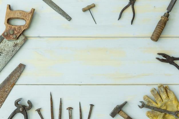 Ferramentas antigas na luz de fundo de madeira