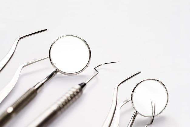 Ferramentas básicas de dentista em fundo branco.