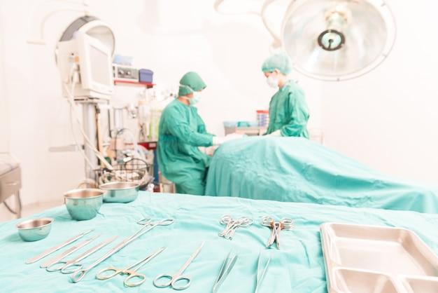 Ferramentas cirúrgicas e uma equipe cirúrgica estão trabalhando em uma sala de cirurgia. foco seletivo na ferramenta