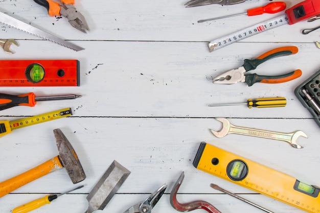 Ferramentas da construção da mão velha em uma superfície de madeira.