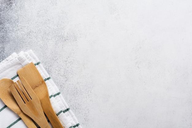 Ferramentas de bambu de cozinha garfo e colher em guardanapo de linho em um velho concreto cinza