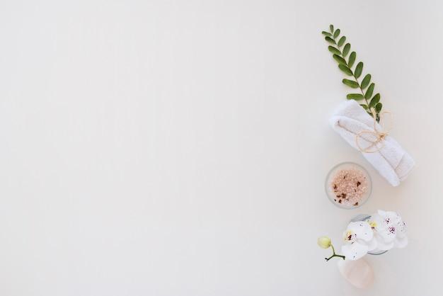 Ferramentas de banho e sal rosa colocado na mesa branca