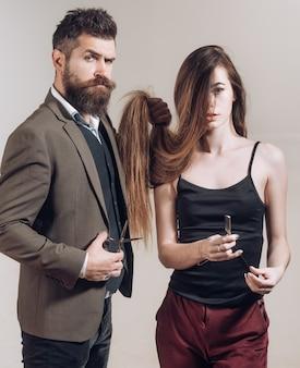 Ferramentas de barbearia na parede cinza. homem barbudo anm mulher com cabelo comprido. projeto da barbearia. barbearia vintage. gilete afiada. barbearia. tesouras de barbeiro.