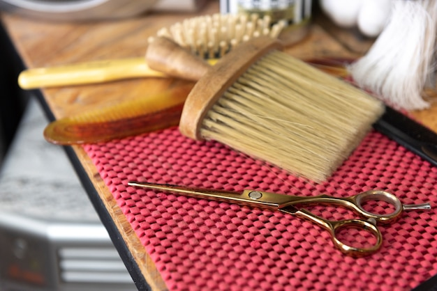 Ferramentas de barbearia vintage na almofada vermelha. espaço de trabalho vintage de cabeleireiro