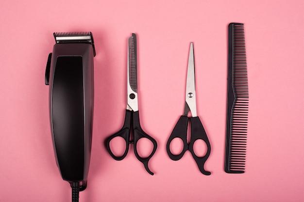 Ferramentas de cabeleireiro, ferramentas de corte de cabelo, máquina de cortar cabelo e tesoura na vista superior do fundo rosa.
