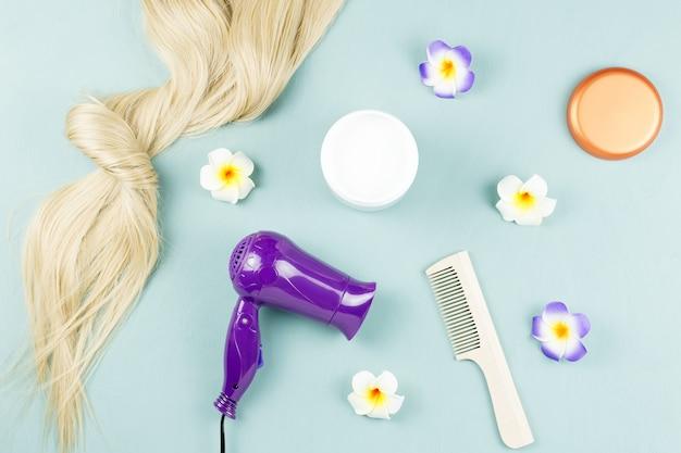Ferramentas de cabeleireiro, máscara nutritiva e extensões de cabelo em madeira azul