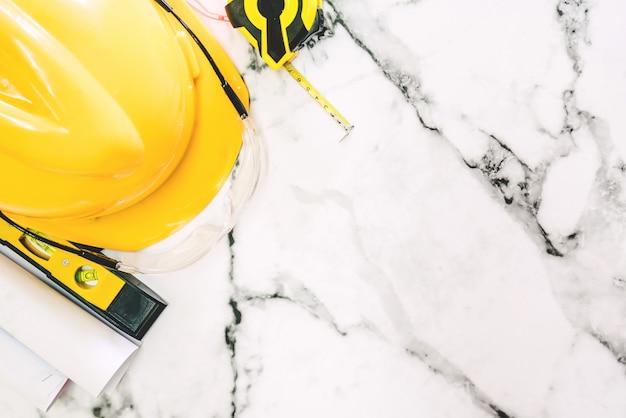 Ferramentas de construção com segurança de capacete em fundo de mármore branco