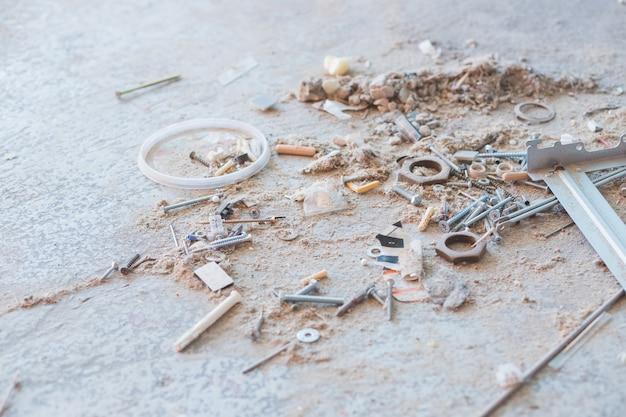 Ferramentas de construção, detritos de construção, uma pilha de pedras de concreto, poeira, entulho, fragmentos de paredes de edifícios, inserções metálicas. andar do prédio destruído