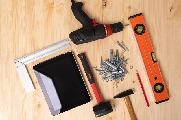 Ferramentas de construção e um tablet digital deite-se sobre uma mesa de madeira clara