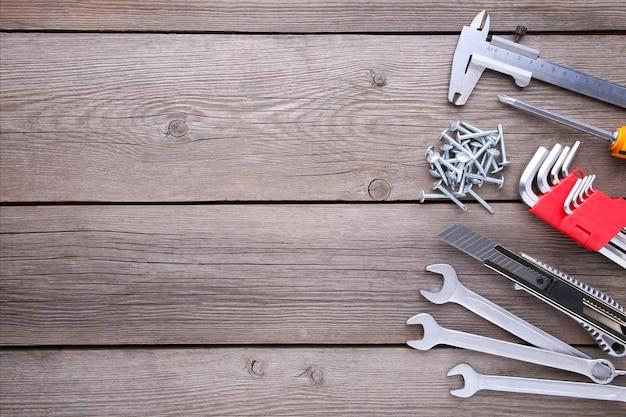 Ferramentas de construção em uma mesa de madeira cinza.