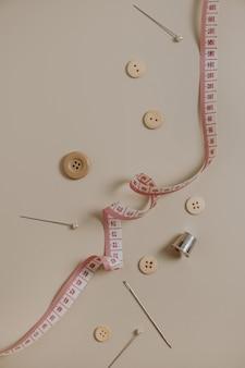 Ferramentas de costura: botões, carretel, dedal, fita métrica, agulhas em fundo bege neutro.