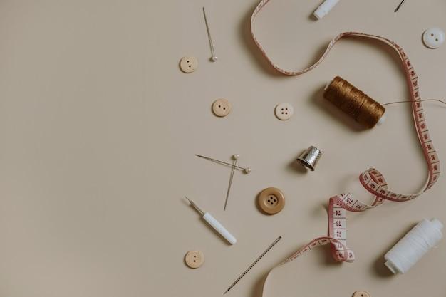 Ferramentas de costura: botões, carretel, dedal, fita métrica em bege neutro