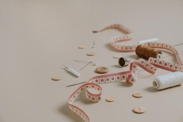 Ferramentas de costura: botões, carretel, dedal, fita métrica em fundo bege neutro.
