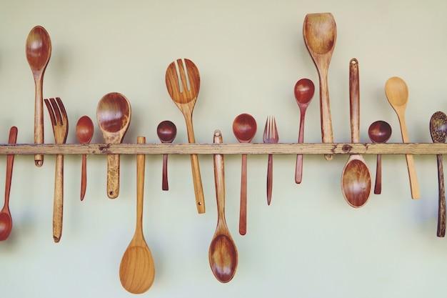 Ferramentas de cozinha de madeira: colher de pau, garfo de madeira, espátula de madeira, pendurar na parede branca.