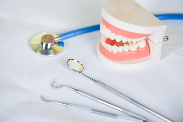 Ferramentas de dentista com instrumentos de odontologia de dentaduras e conceito de controle de higienista dental com modelo de dentes