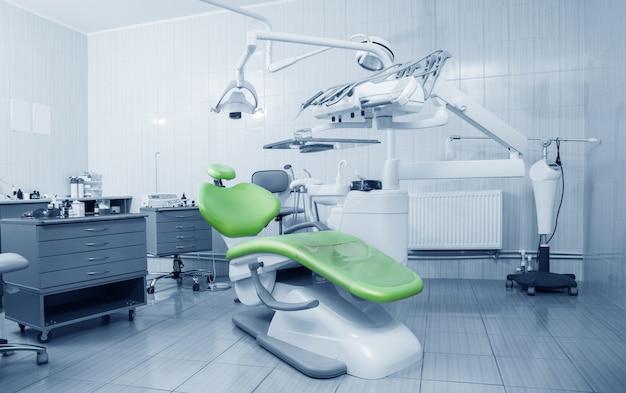 Ferramentas de dentista profissional e cadeira no consultório odontológico