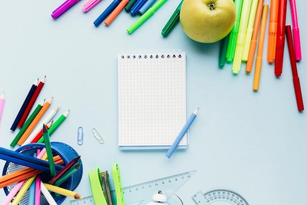 Ferramentas de desenho coloridas espalhadas em torno do bloco de notas em branco na mesa azul