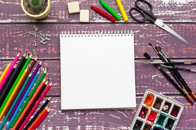 Ferramentas de desenho, material estacionário, local de trabalho do artista. tintas aquarela e bloco de notas em branco na mesa de madeira