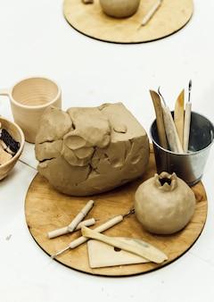 Ferramentas de escultura de closeup colocadas na mesa, pilhas de argila, alguns perfis.