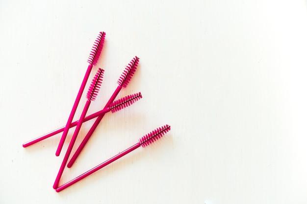 Ferramentas de extensão de cílios, pinças prateadas e pincéis rosa em branco, vista superior