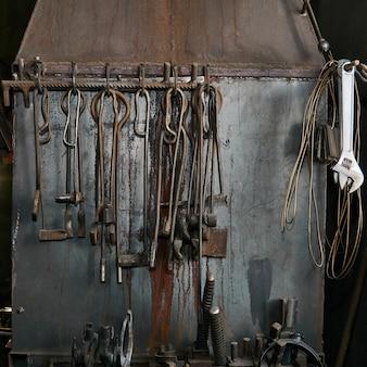Ferramentas de ferreiro e serralheiro vintage em ferro bruto penduradas na parede de metal da fornalha